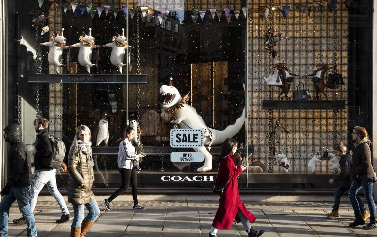 Pedestrians walk past a store front advertising sale discounts on Regent street in central London