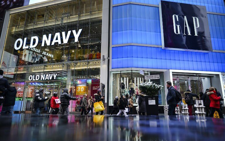 Pedestrians walk past Old Navy and GAP stores in Times Square, in New York City.