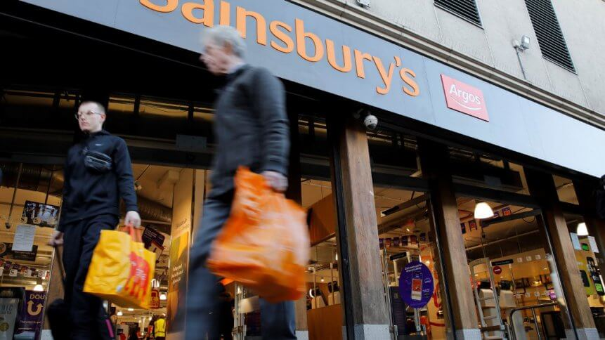 Pedestrians walk past a sign above the entrance to a Sainsbury's supermarket store in London.