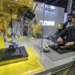 A man races against the speed of a FANUC robot sorting colored objects at the 2020 Consumer Electronics Show