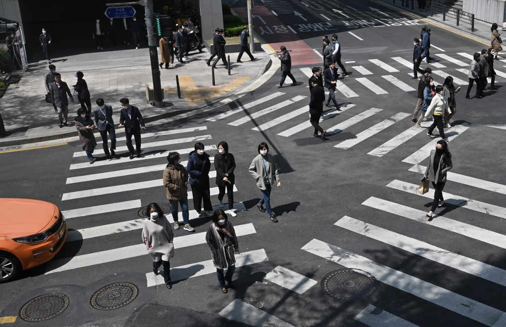 Pedestrians wearing face masks cross the road in Seoul, South Korea