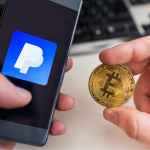 Man holding Bitcoin coin and in other hand smartphone with Paypal application.