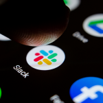 Close up photo Slack app on the smartphone screen and a finger launching it. The top app for communication and collaboration.