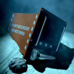 A regular aviation flight recorder black box painted in orange underwater resting on the ocean floor